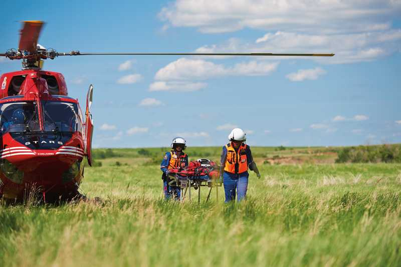 Stars helicopter paramedics carry a stretcher from their helicopter