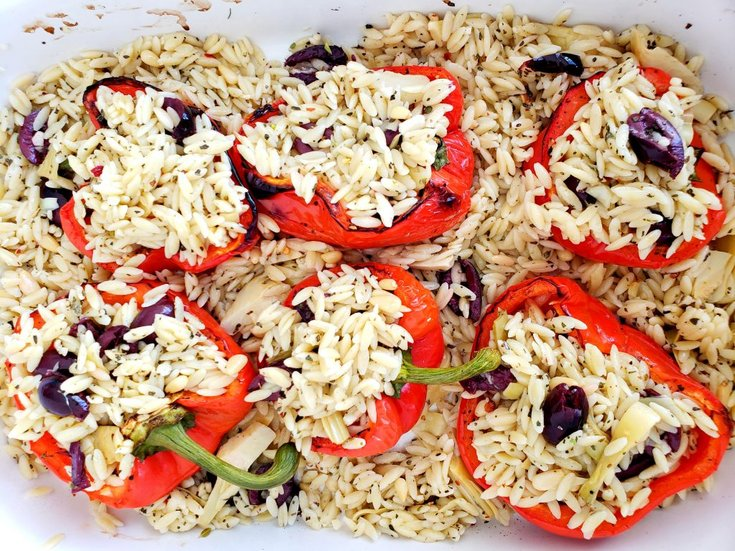 Casserole dish with red peppers stuffed with lemon orzo