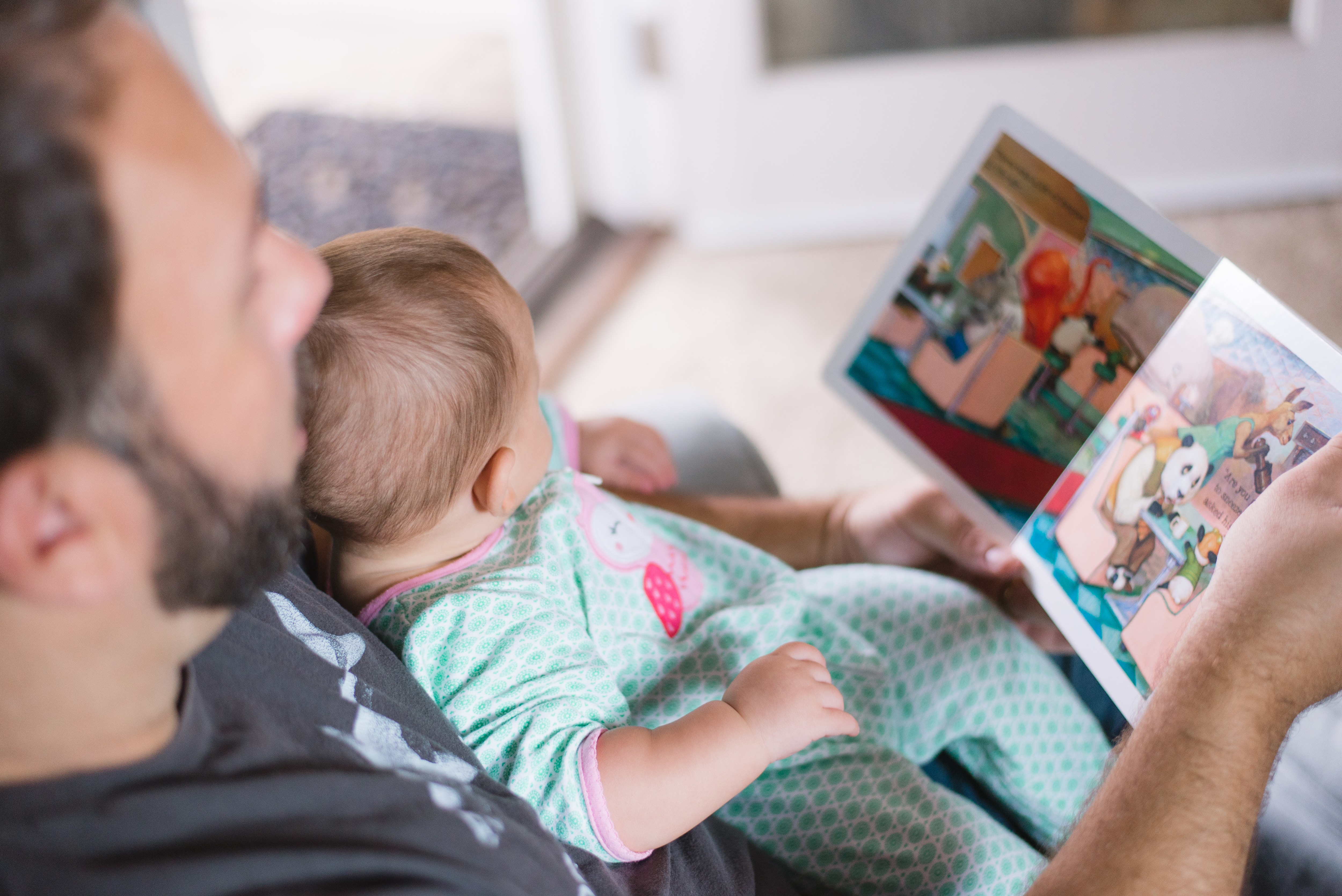 Stock image of dad reading book for child