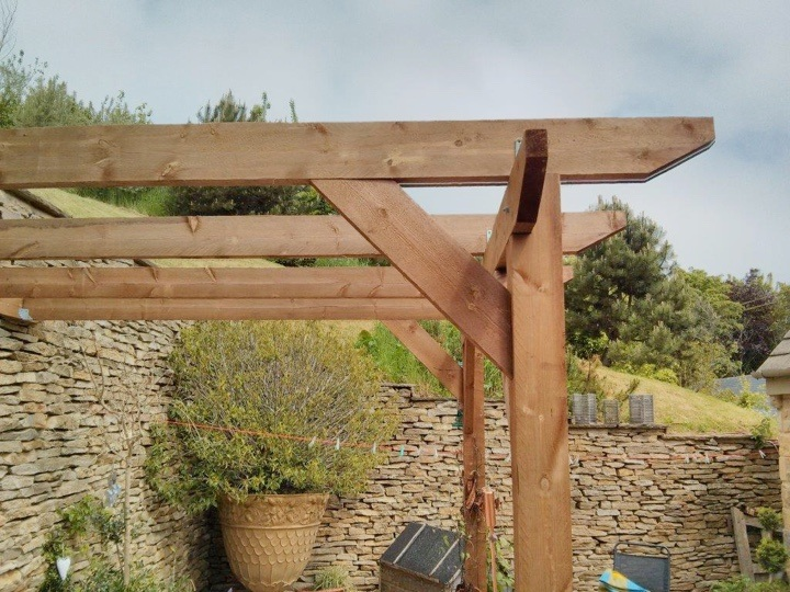 A close up of a lean-to pergola, with hills in the distance
