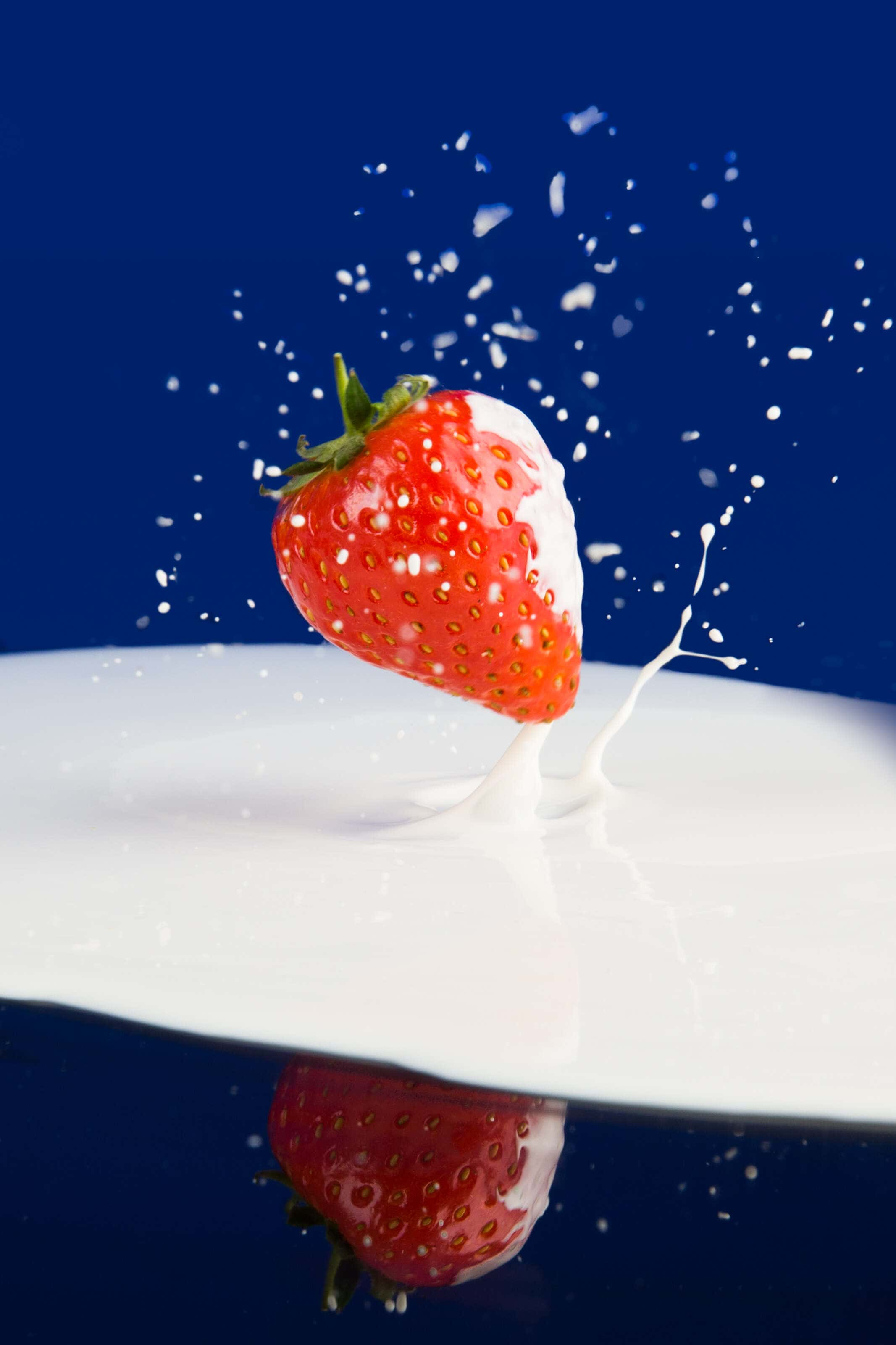 A strawbery falling onto cream on a mirrored surface.