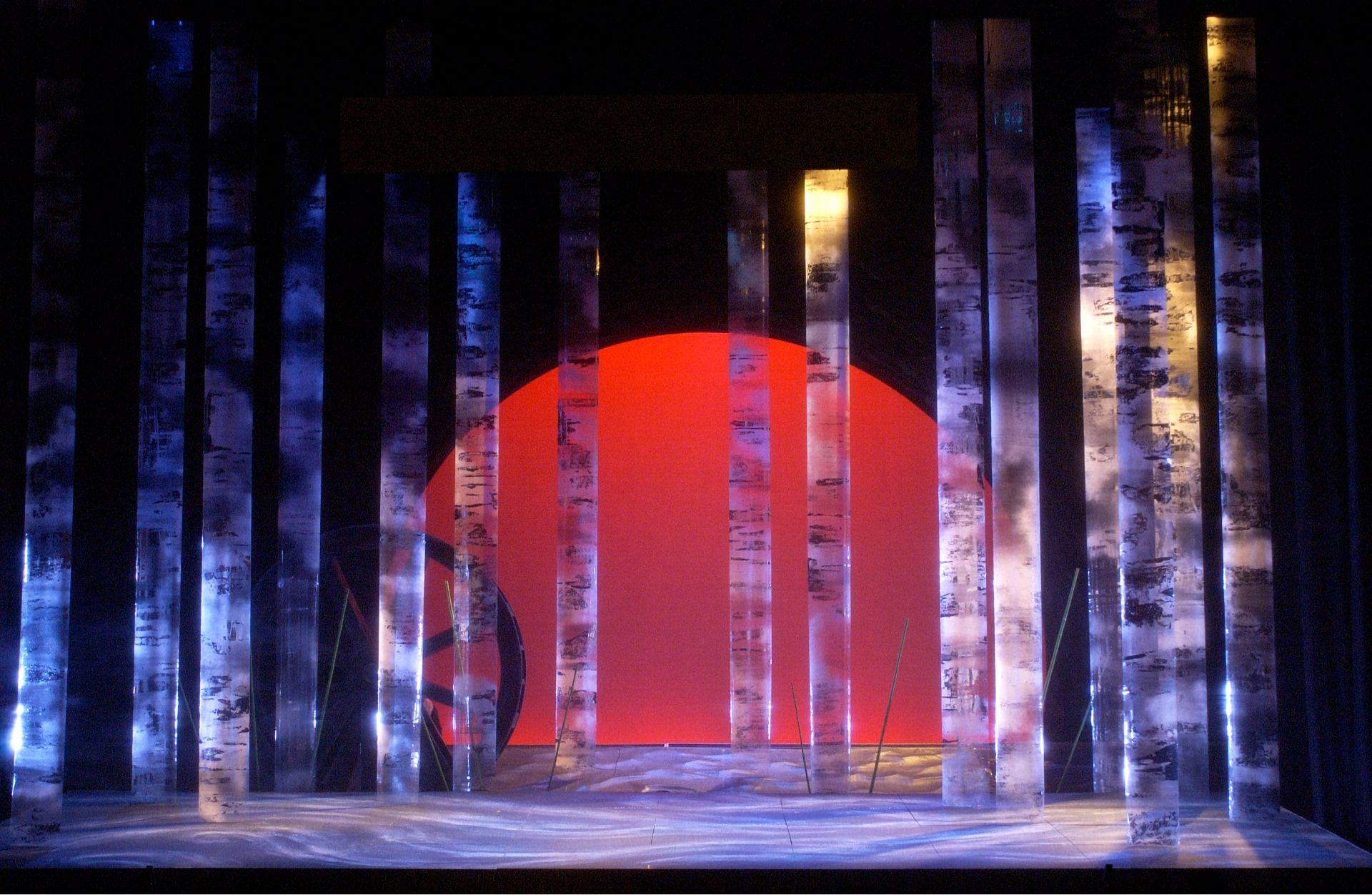 Forest of plexiglass columns painted in swirling light, against mill wheel and red sunrise behind.