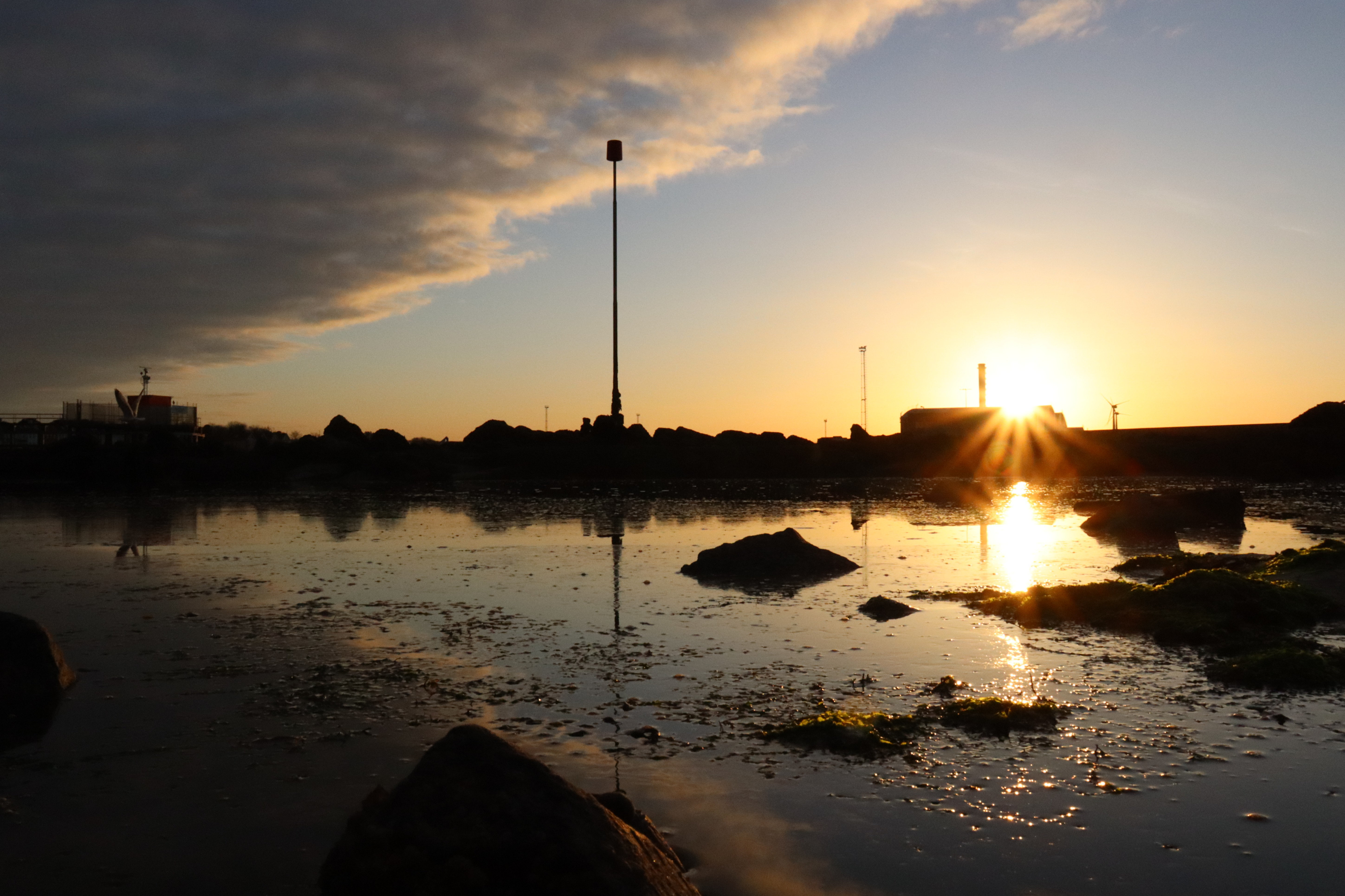 Sun rising over Shoreham port that is reflecting a wave of clouds into the water below.