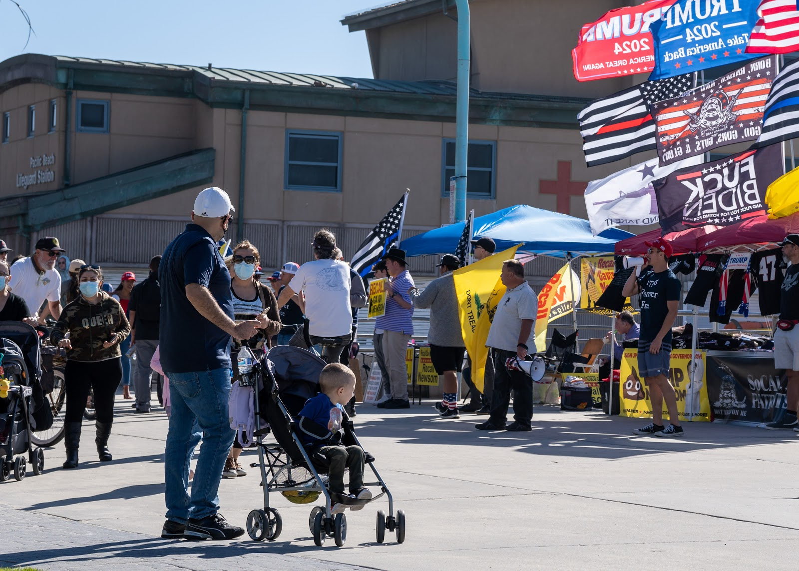 A toddler looks on at the display, while two men with bullhorns take turns comparing the governor to various dictators throughout history. Among the flags for sale is a blue Trump 2024 flag, with the text 'Take America Back' just below the intended year. At the time of writing, Trump has not announced his candidacy.