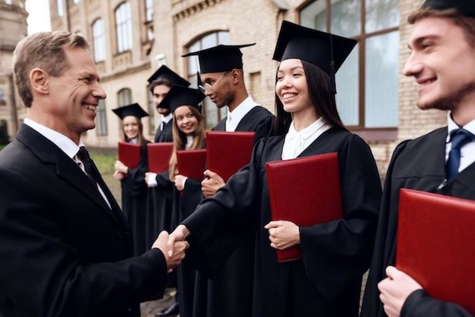 A man smiling and shaking hand with a student, who's dressed for a graduation ceremony