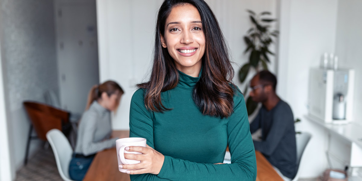 A data analyst standing holding a mug of tea, smiling at the camera