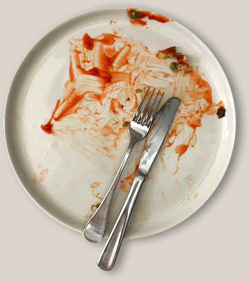 A plate with the aftermath of a delicious ketchup-y dinner.