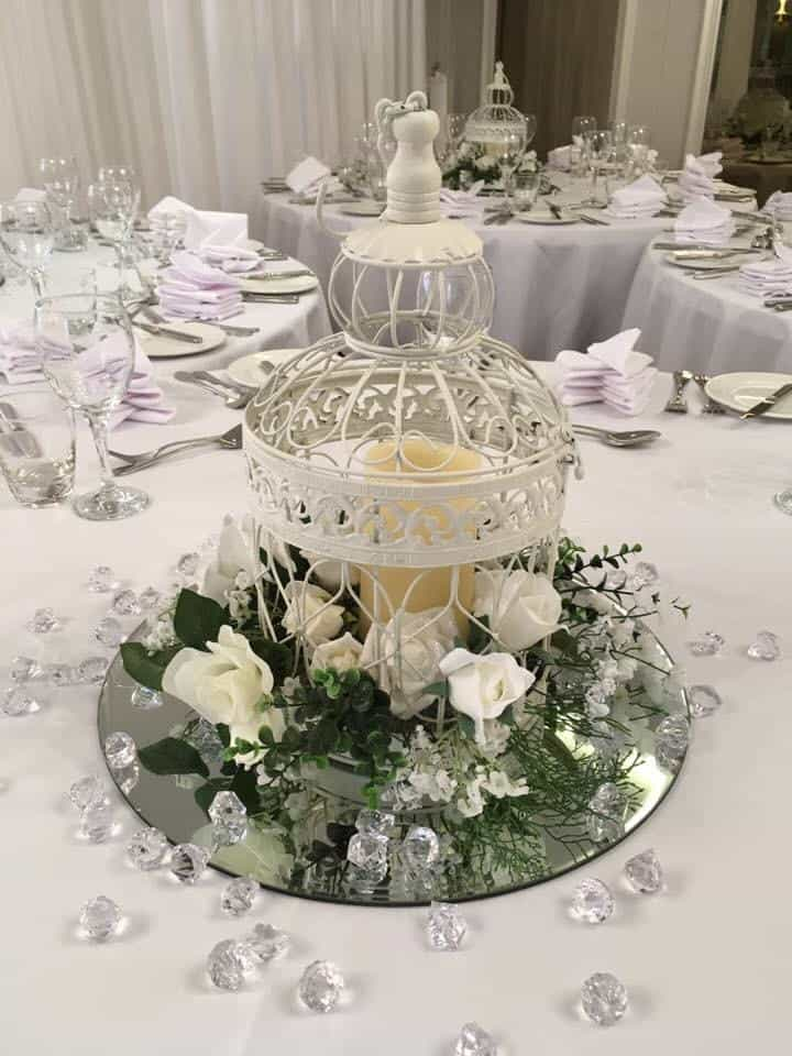 Wedding breakfast table centrepiece birdcage with cangle inside and little sparkling gems around it