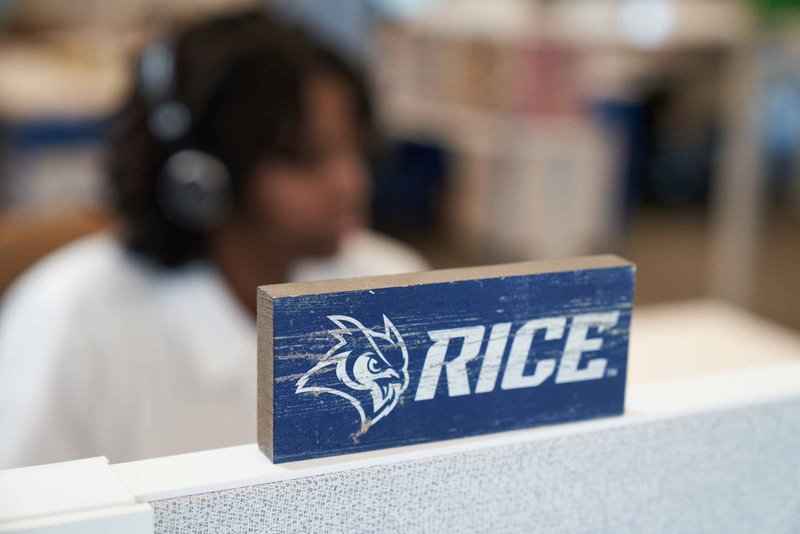 Wooden block with Rice name and mascot on it set on top of a cubicle with student listening to headphones in the background