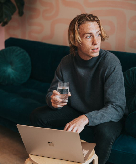 Man with laptop looking to the left while holding a glass of water