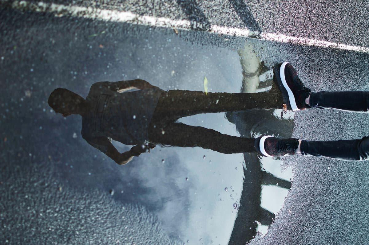 Um rapaz em cima de uma poça olhando para o seu reflexo