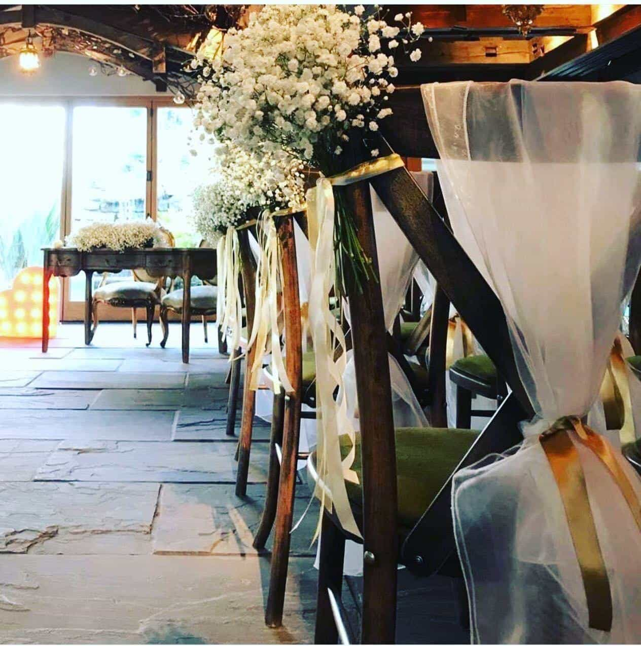 Wedding chair dressing with white floral and silk drapes
