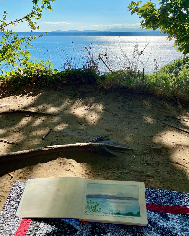 My sketchbook open on a blanket, with a sketch of the water and mountains also pictured beyond.