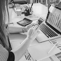 woman tapping a smartphone at her office desk