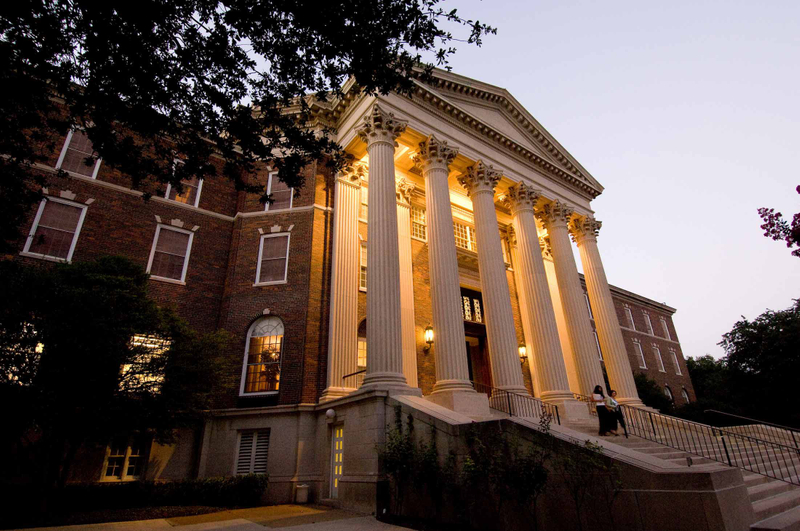 Two students walking down the lit staircase of SMU's Dallas Hall at dusk