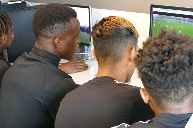 Football team watching video replays on laptop