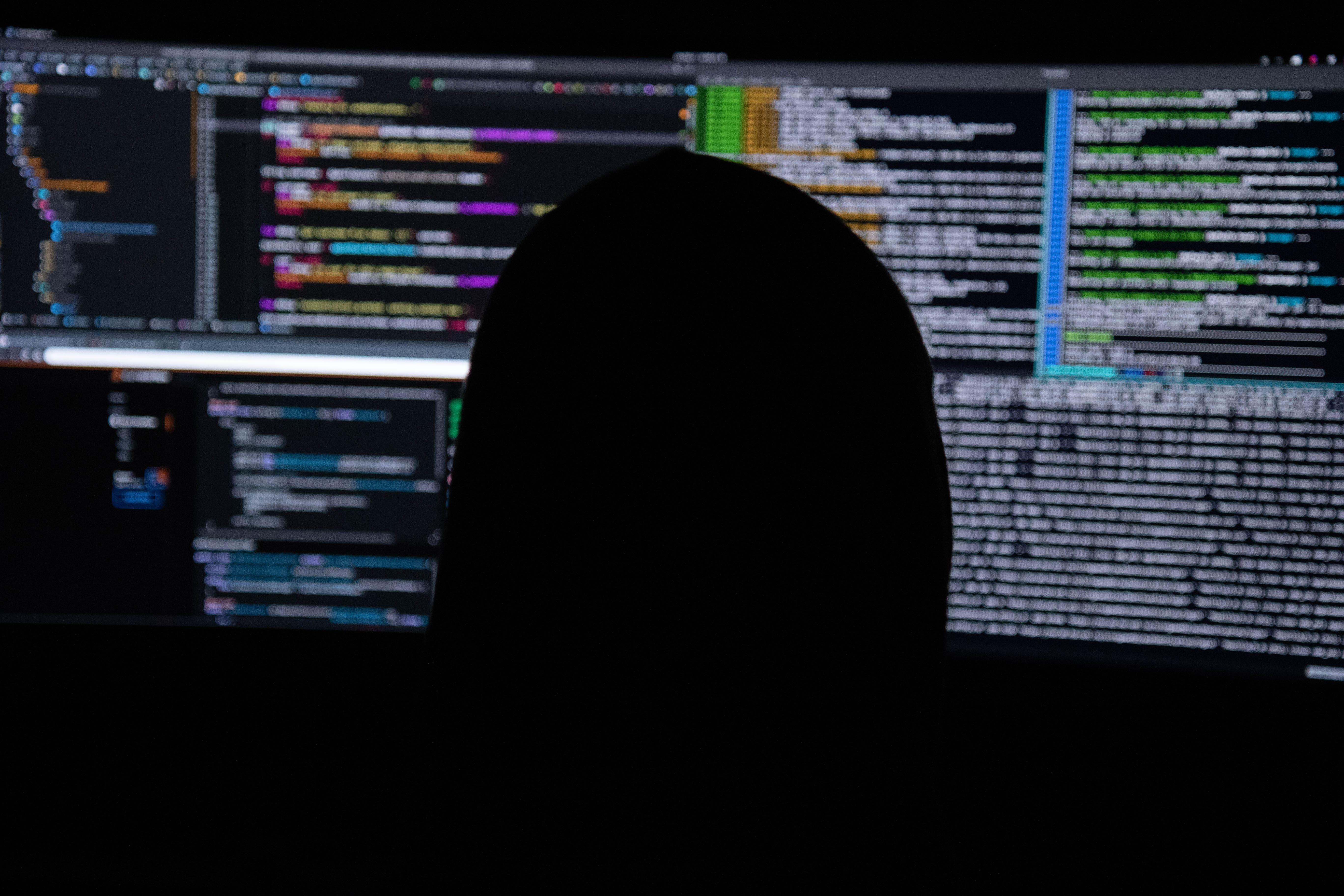 Pessoa utilizando um computador, com uma blusa preta e a tela do notebook com vários terminais abertos