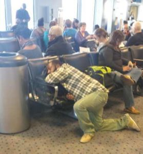 man sleeping with his head on chair during layover flight