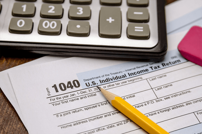 A calculator in front of a 1040 tax return with a pencil nearby.