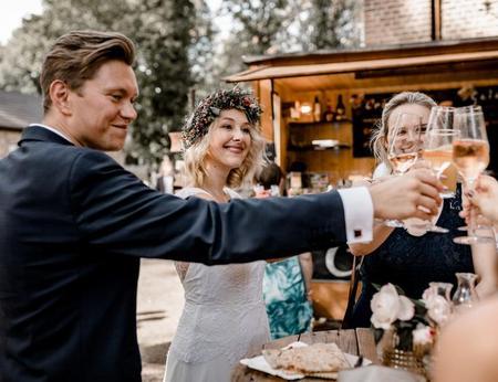 Hochzeitspaar stößt über einem Crêpe mit Hochzeitsgästen vor dem Hintergrund eines gemütlichen Crepestandes an