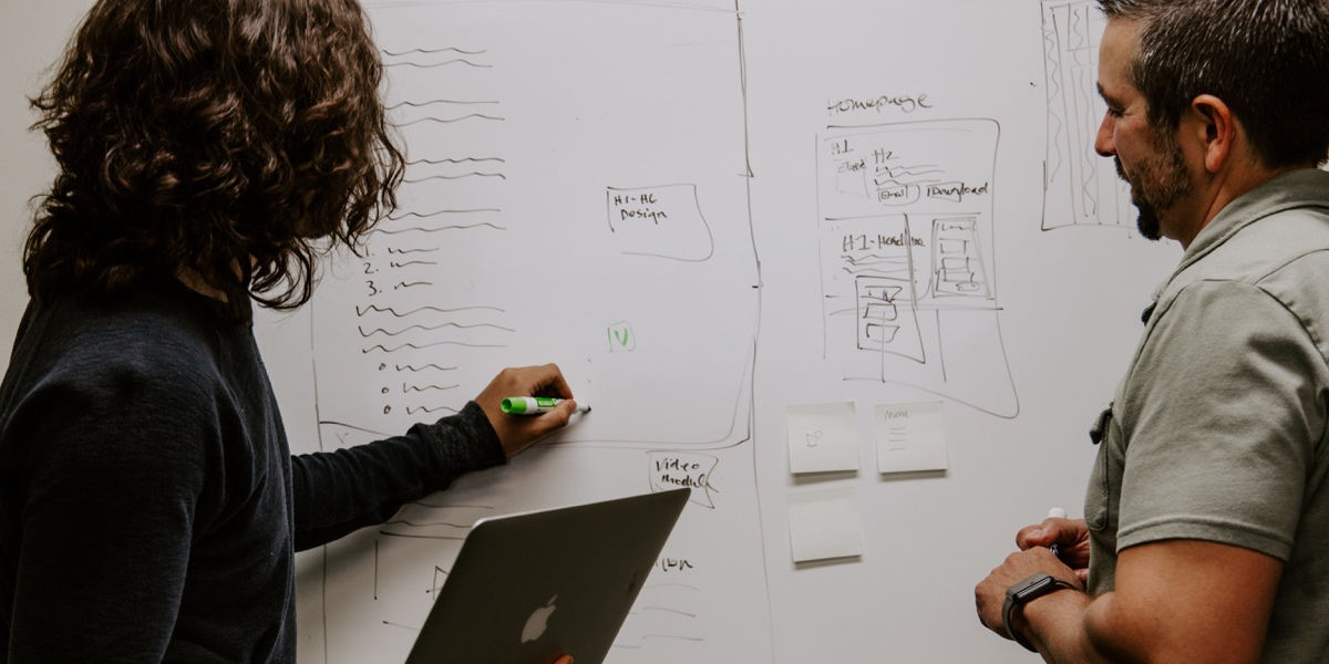 Two designers standing at a white board. One is drawing and holding an open laptop, and the other is observing