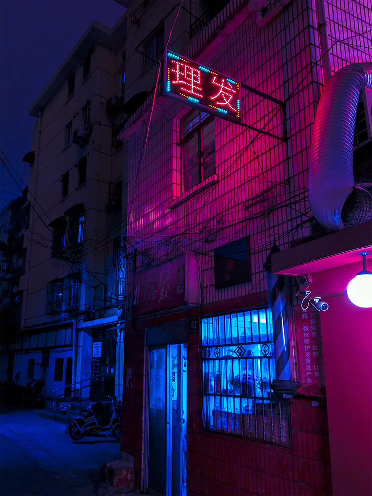 A neon alley with a Chinese sign