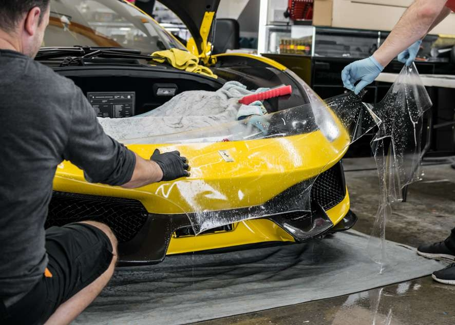 Paint protection film (PPF) being applied to front bumper of yellow Ferrari 488 Pista