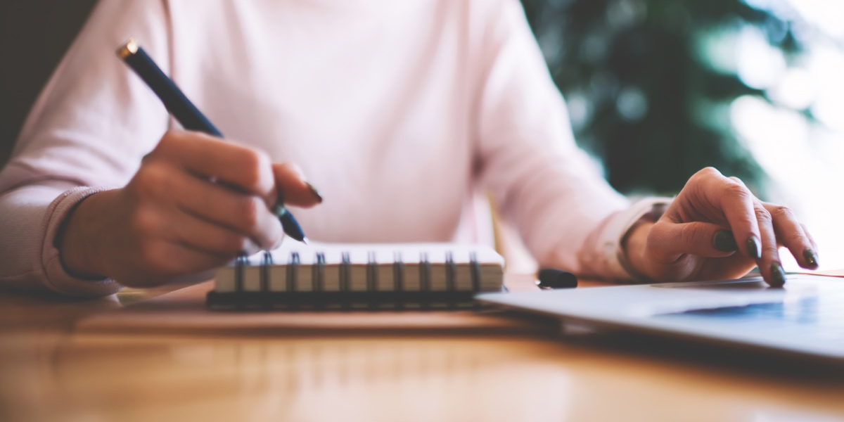 Close up of a person sitting at a desk with one hand hovering over a laptop keyboard and the other writing with a pen on a notepad