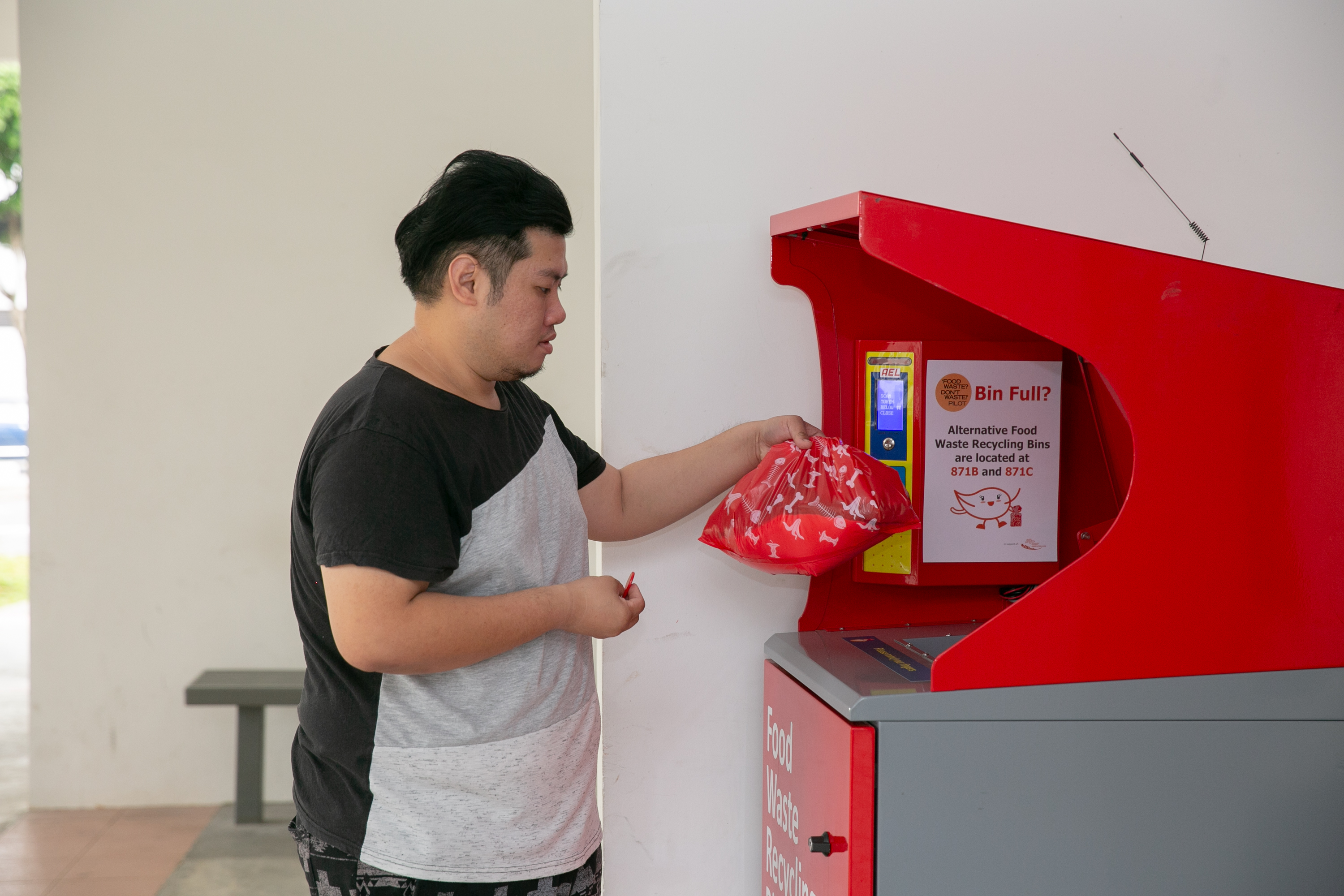 A resident disposes of food waste into a food waste recycling bin