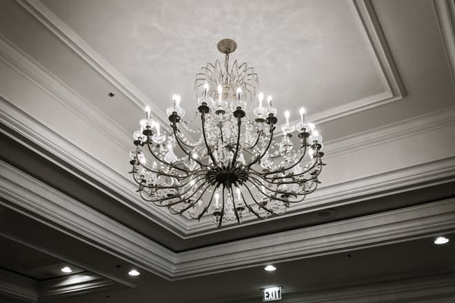 A crystal and brass chandelier casts intricate shadows and reflections against a ballroom ceiling.