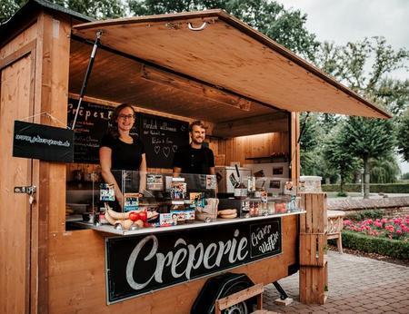 Schön dekorierter mobiler Crepesstand mit zwei Mitarbeitern
