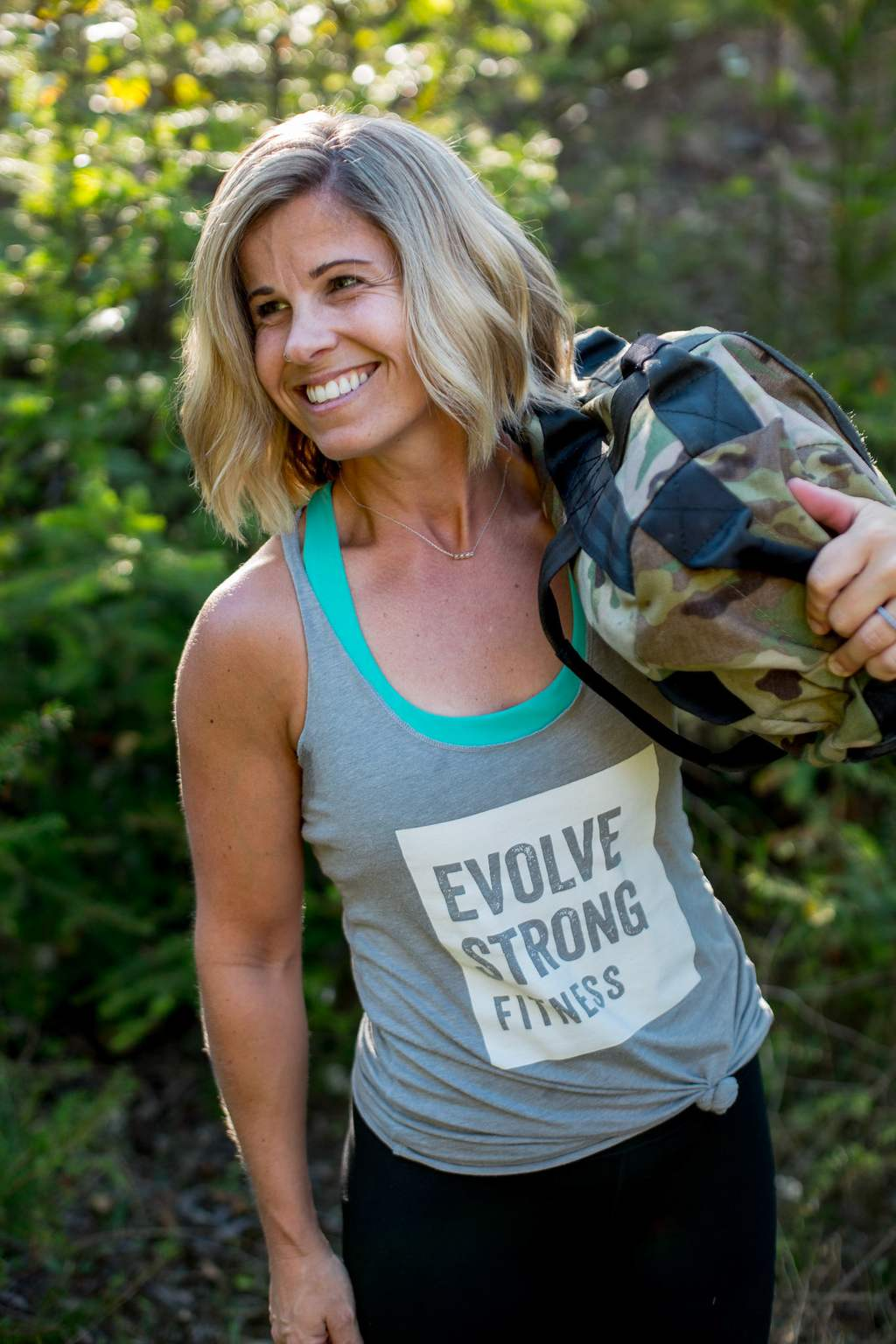 EVOLVE Strong Fitness coach Holly outdoor workout with sandbag