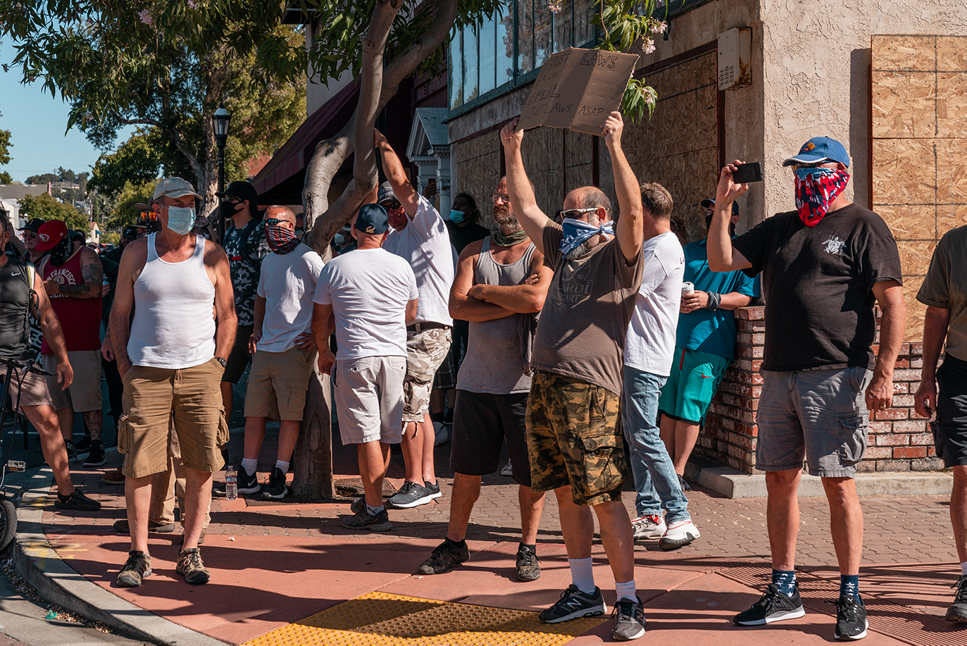 A group of counter-protesters watches as several hundred march from the Contra Costa County Courthouse to the Waterfront Park in Martinez, Calif., on Sunday, July 12, 2020.