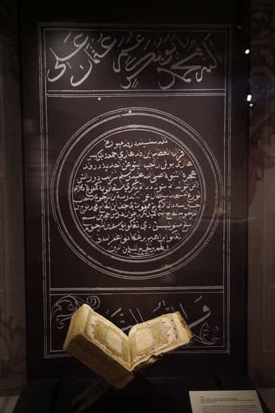 A tall showcase with the Qur'an, opened up to illuminated manuscripts. A black and white graphic with similar illuminated manscript decorates the back of the showcase.