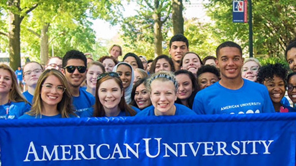 A group of people AU's students standing and smiling behind a flag written American University