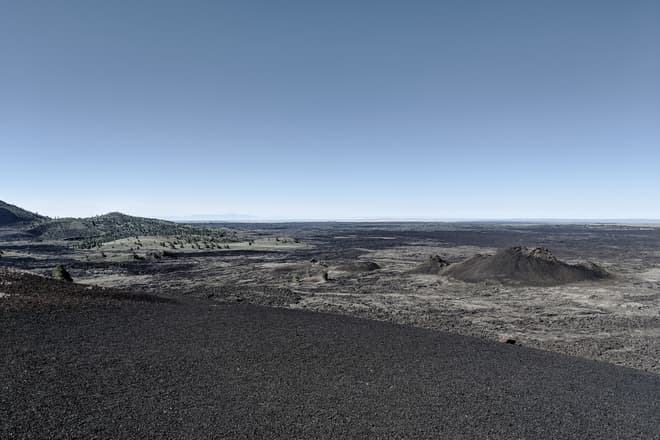 Looking out across a jagged, black basalt field from the top of a volcanic cinder cone. A row of low, steep-sided splatter cones can be seen mid-distance.