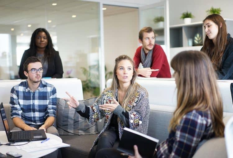 Gruppe von Mitarbeitern diskutieren in Seminarraum