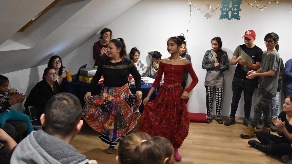 Két táncoló lány, körben nézik őket és tapsolnak