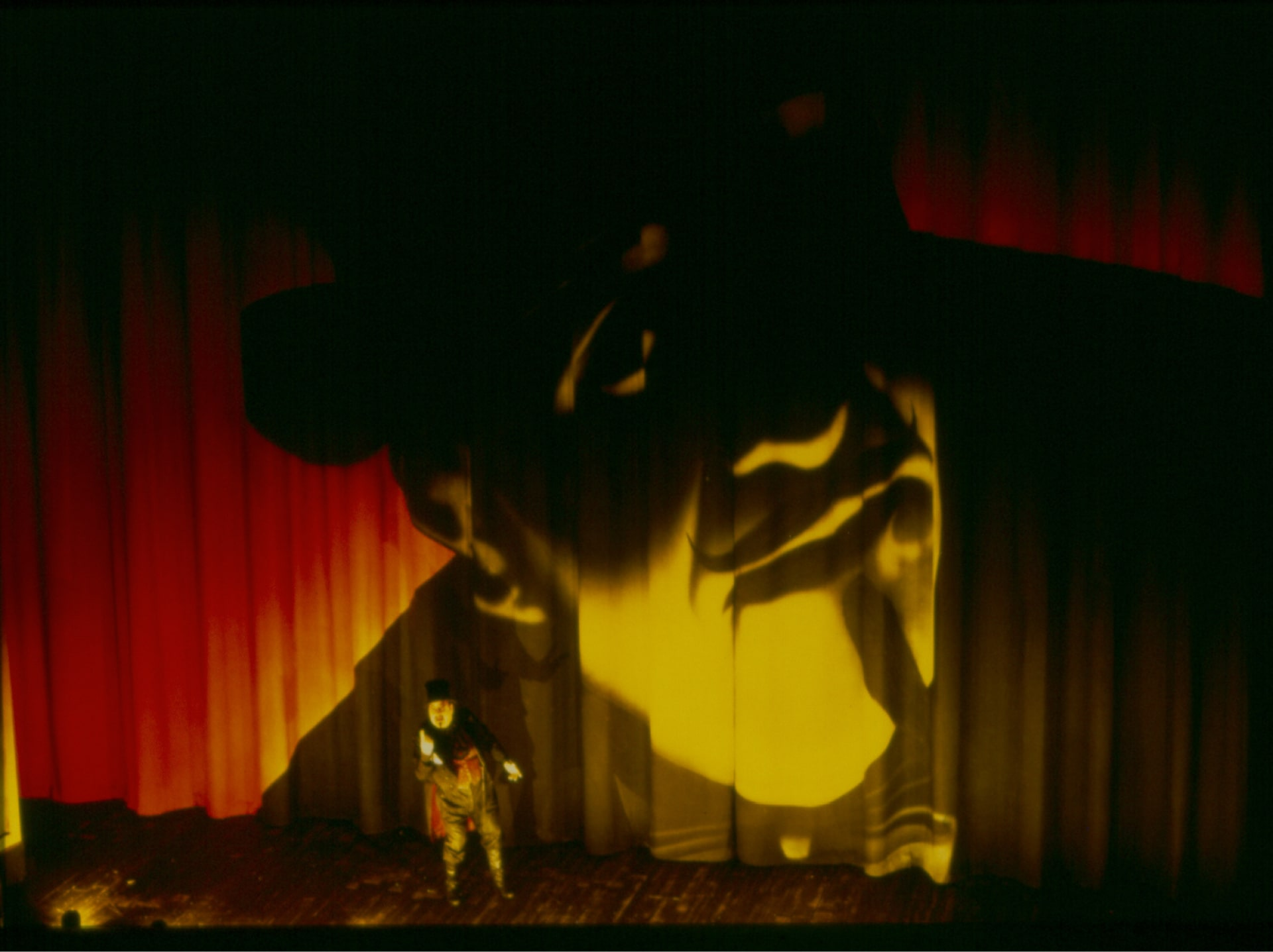 Magician in top hat stands dwarfed on foot lit stage in front of giant image of self painted on curtain.
