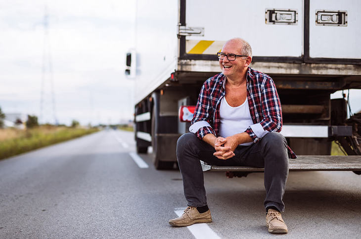 A man sitting on the back of a truck