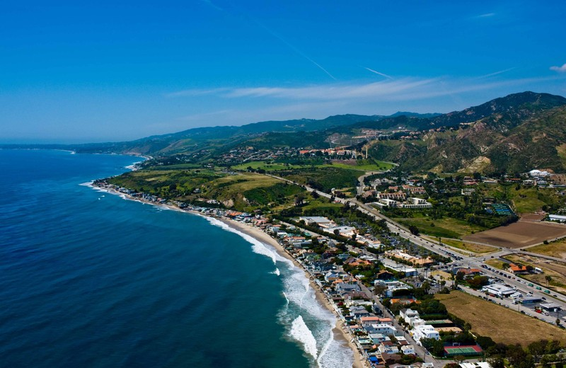 Aerial view of Pepperdine University malibu campus showing waves breaking on the coastline and a green hillside