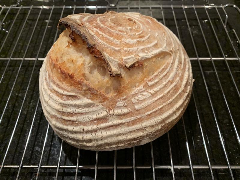 A dome shaped sourdough loaf o. A cooling rack.