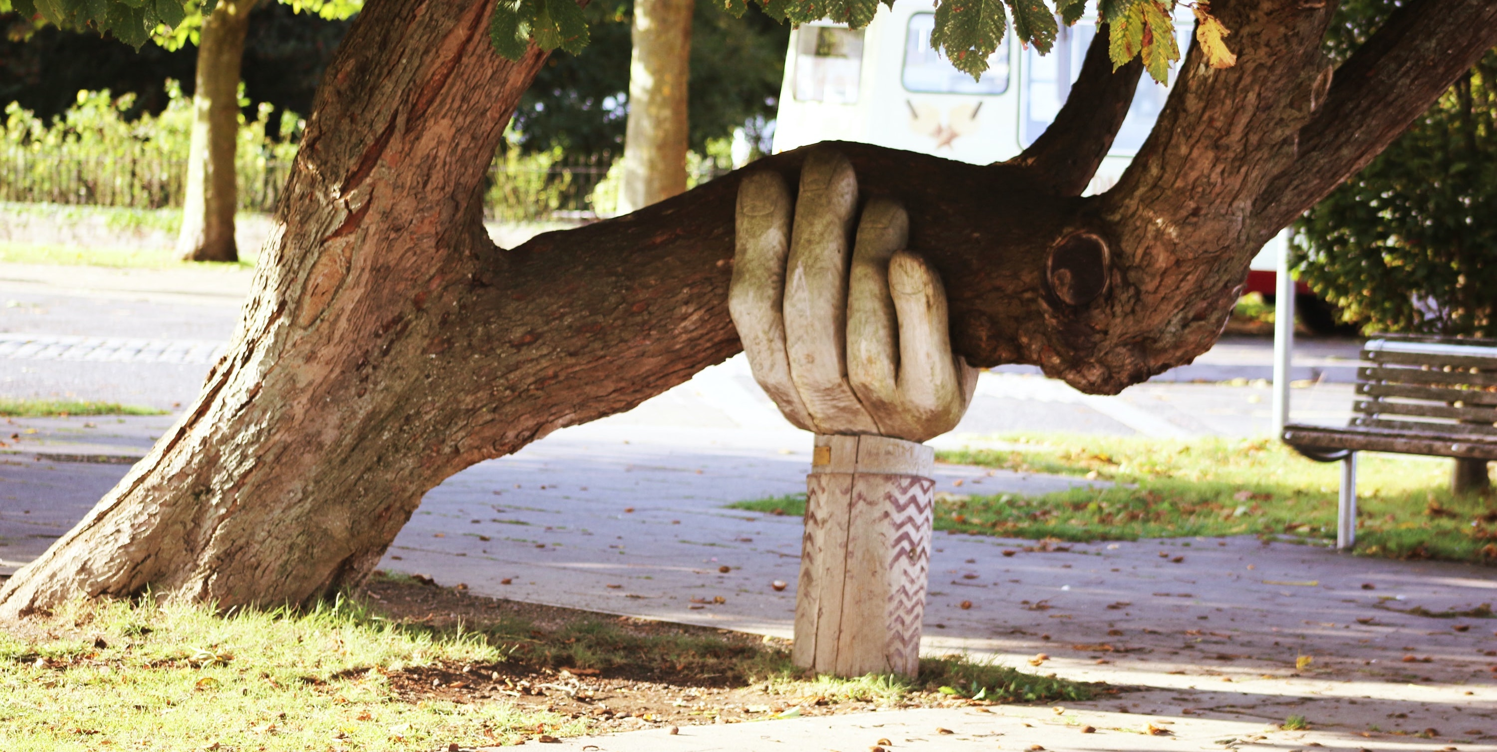 A large, carved, wooden hand supporting a tree that has nearly fallen over