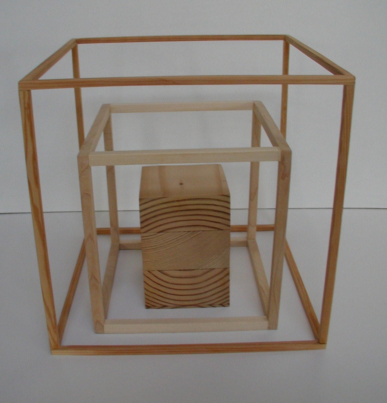 cube of wood inside two wood cube frames