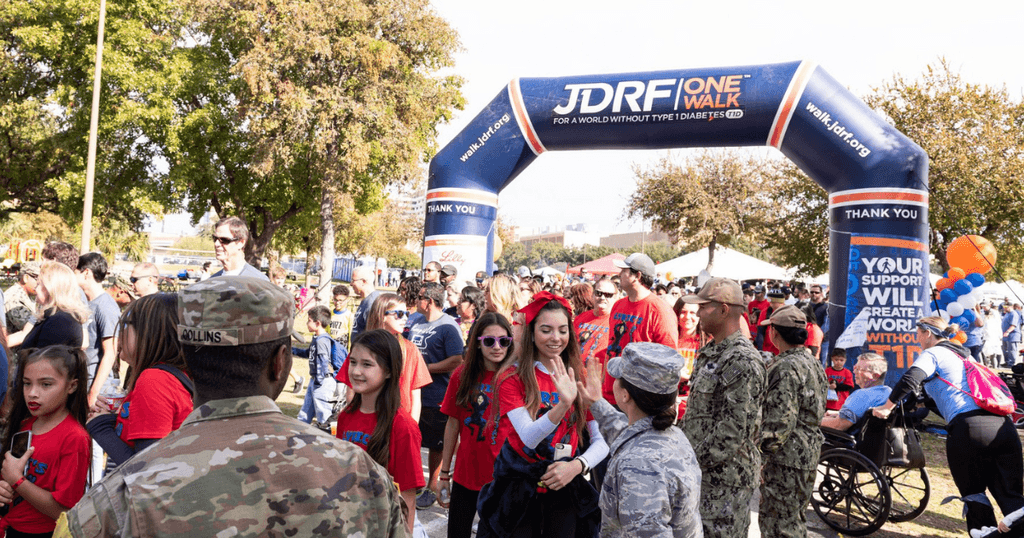 A large group of people are taking part in a JDRF One Walk and high fiving as they walk under a branded JDRF arch