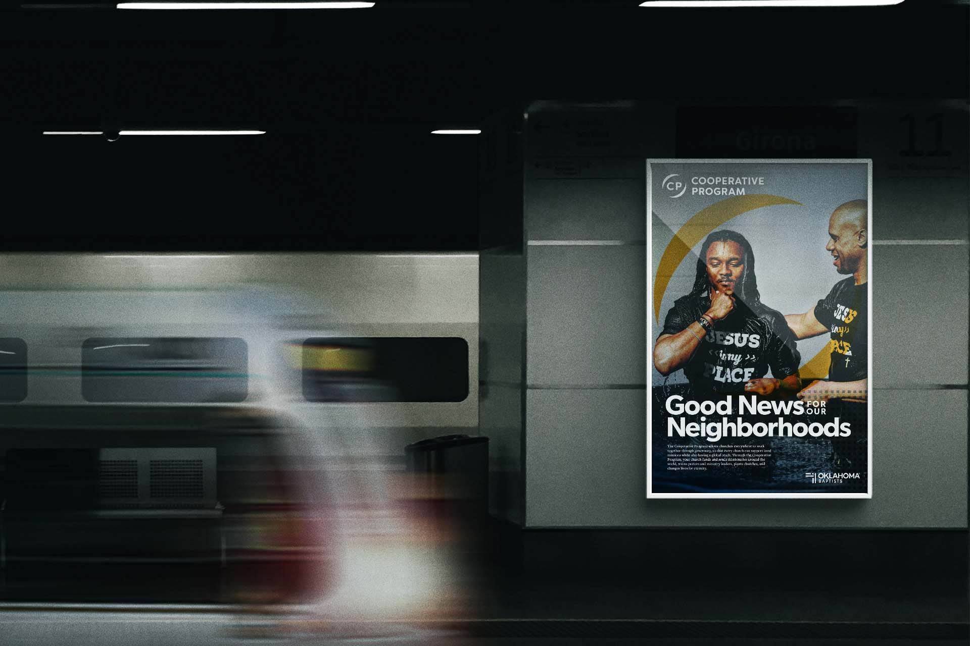 A poster displayed in a dark subway, showing a young man being baptized at a NAMB-funded church plant.