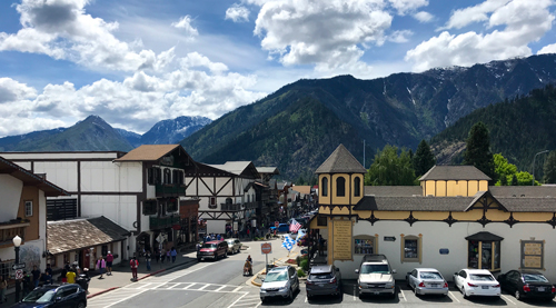 Leavenworth, WA: a cozy street of Bavarian-style buildings with 3 mountains looming close behind