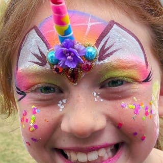 A colourful and glittery unicorn design on a little girl's happy face. This design also features a horn attached to the forehead with adhesive. Click to view at full size.