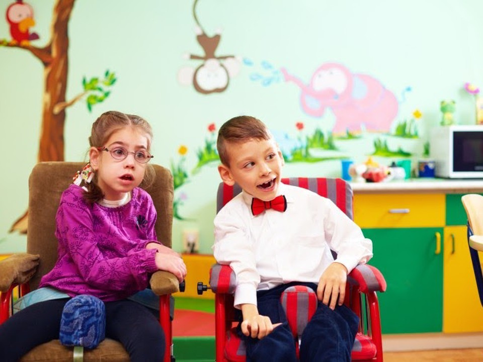 Two children with special needs sit in a classroom.