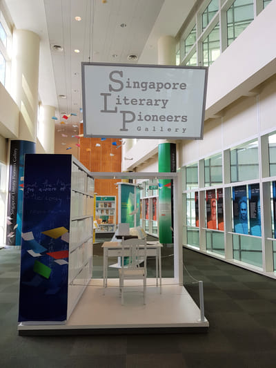 The entrance of the exhibition, with the title sign hanging from above. A display bookshelf with a white table and chair are in the front. A typewriter is on the table.
